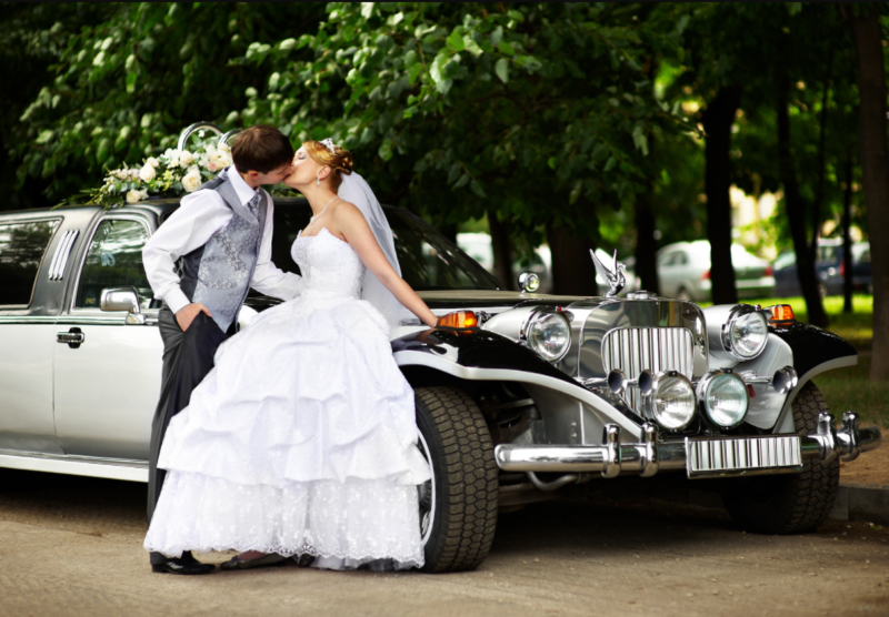 Wedding Couple Standing Next To Limo